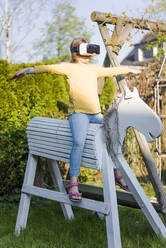 Girl practicing on wooden horse in garden wearing VR glasses - MOEF02285