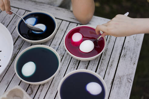 Close-up of two girls dyeing Easter eggs in garden - MOEF02288