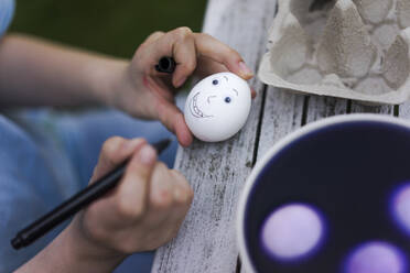 Close-up of girl painting face on Easter egg on garden table - MOEF02291