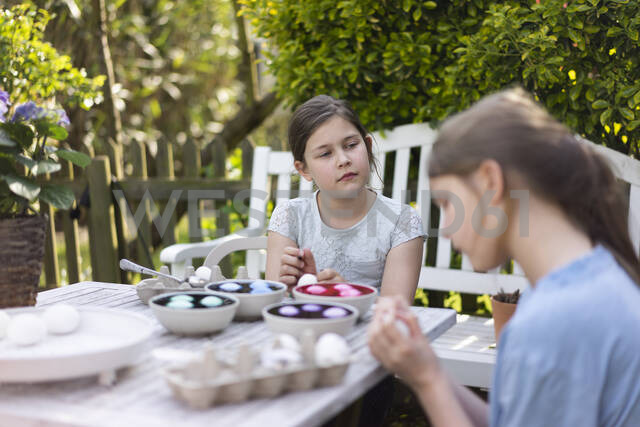 Two girls dyeing Easter eggs on garden table - MOEF02294 - Robijn Page/Westend61