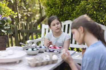 Two girls dyeing Easter eggs on garden table - MOEF02294