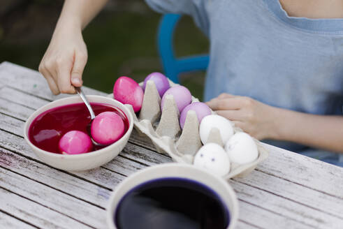 Close-up of girl dyeing Easter eggs in garden - MOEF02297