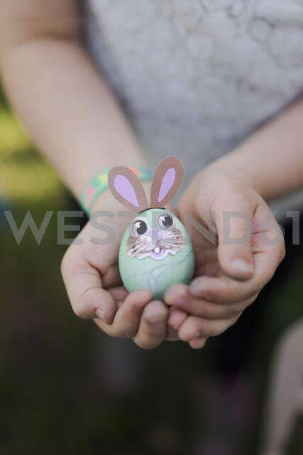 Close-up of girl holding decorated Easter egg - MOEF02300 - Robijn Page/Westend61