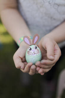 Close-up of girl holding decorated Easter egg - MOEF02300