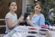 Portrait of two girls decorating Easter eggs on garden table - MOEF02303