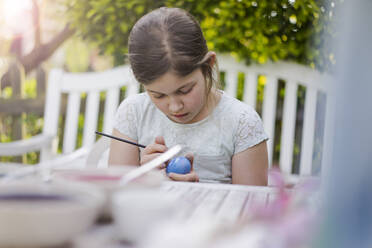 Girl painting Easter egg on garden table - MOEF02306