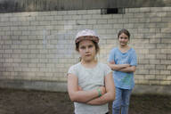 Portrait of two girls standing in front of a brick wall - MOEF02309