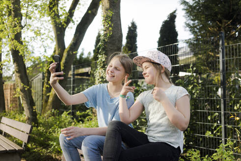 Two happy girls sitting on a park bench taking a selfie - MOEF02312