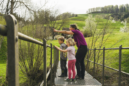 Mother with two children on a bridge in the countryside - FBAF00766