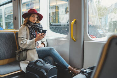 Young woman using cell phone in a tram - FBAF00792