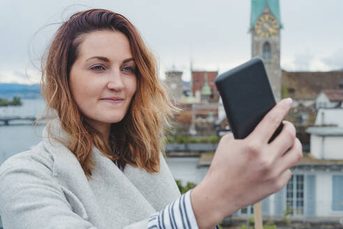 Young woman taking smartphone picture in the city, Zurich, Switzerland - FBAF00804