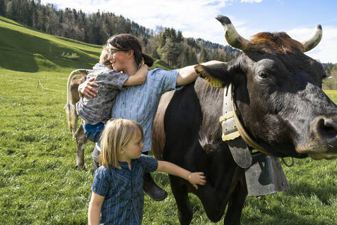 Mother with two children on cow pasture - FBAF00828