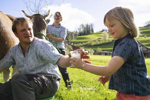 Farmer giving his daughter a glass of fresh milk from a cow on pasture - FBAF00843