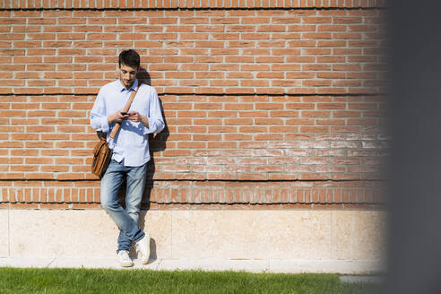Young man using smartphone in the city - GIOF06510