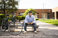 Young man with bicycle using smartphone and listening music - GIOF06528