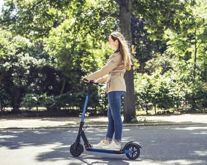 junge Frau mit e - scooter, Elektroroller, Roller, Elektro-Mobilität, Umweltschutz, lifestyle, Berlin, Deutschland - BFRF02029
