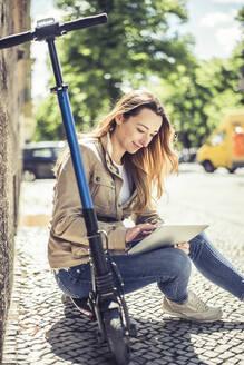 junge Frau mit e - scooter und digital tablet, Elektroroller, Roller, Elektro-Mobilität, Umweltschutz, lifestyle, Berlin, Deutschland - BFRF02035