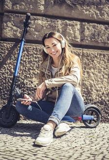 Portrait of happy woman sitting on E-Scooter listening music with headphones and smartphone - BFRF02041