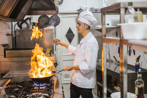 Junior chef with pan of flames in traditional spanish restaurant kitchen - LJF00198