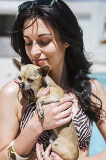Young women with chihuahua at the pool - LJF00237