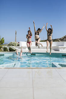 Young women enjoying the summer time at pool, jumping into the water - LJF00252