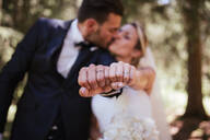 Romantic bride and groom kissing and showing wedding rings in woodland, selective focus on hands - ISF21943