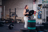 Young woman placing weight plate onto rack in gym - ISF22048