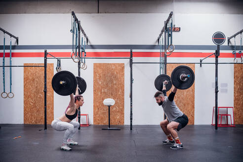 Young couple squatting and lifting barbell in gym - ISF22057