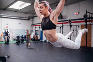 Young woman swinging in mid air in gym - ISF22072