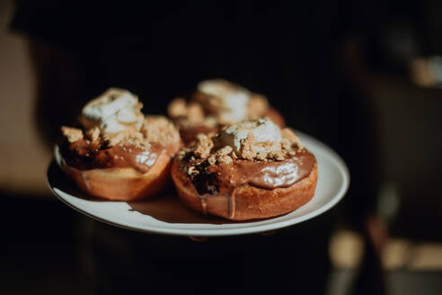 Barista carrying plate of chocolate doughnuts in cafe, cropped close up - ISF22084