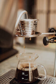 Boiled kettle water pouring into coffee filter and dripping into jug on cafe counter, close up shallow focus - ISF22096