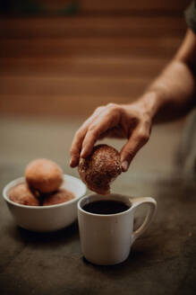 Man dipping doughnut into black coffee at cafe table, cropped shallow focus - ISF22099