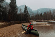 Happy young female canoeist sitting on canoe in river, Yosemite Village, California, USA - ISF22111