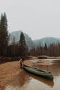 Young female canoeist pulling canoe from river, Yosemite Village, California, USA - ISF22114