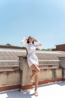 Woman on roof top wearing fashionable white dress - AFVF03431