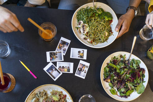 Group of friends having lunch in a restaurant with instant photos on table - AFVF03484