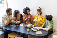 Group of happy friends with an instant camera having lunch in a restaurant - AFVF03493