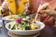 Close-up of people having healthy lunch in a restaurant - AFVF03508