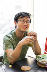 Portrait of a smiling man sitting at table in a restaurant having healthy lunch - AFVF03514