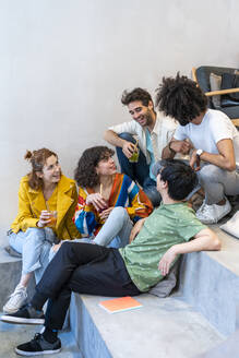Group of friends sitting on stairs having a drink - AFVF03517