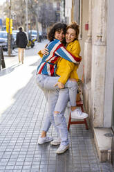 Two carefree young women hugging in the city - AFVF03529