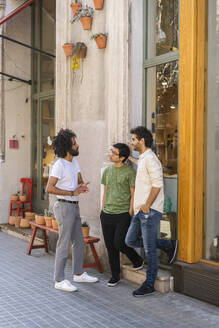 Three young men talking in the city - AFVF03532