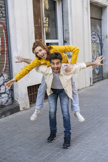 Happy man giving girlfriend a piggyback ride on pavement in the city - AFVF03535
