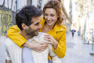 Man giving girlfriend a piggyback ride on pavement in the city - AFVF03538