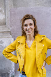 Portrait of a smiling young woman wearing a yellow jacket - AFVF03541