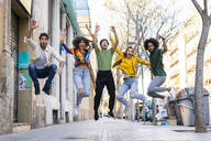 Happy group of friends having fun in the city jumping mid-air - AFVF03547