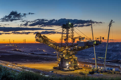 High angle view of bucket-wheel excavator at mine against sky during sunset - FR00856