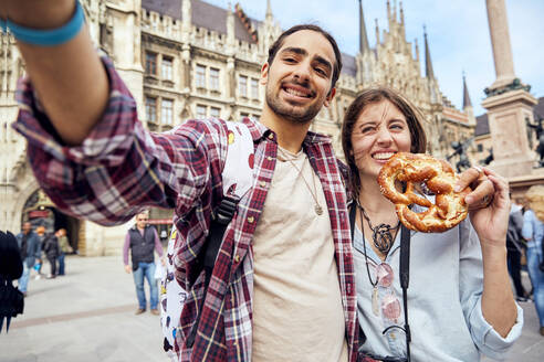 Young couple taking a selfie with brezel in Munich, Germany - SUF00584