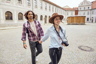 Young tourist couple walking in courtyard of Munich Residenz, Munich, Germany - SUF00587