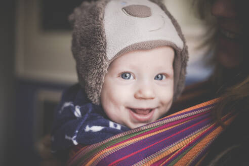 Portrait of happy baby boy in a sling - IHF00153
